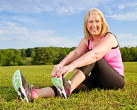 Middle-aged woman in her 40s stretching. For exercise outdoors Royalty Free Stock Image