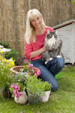 Middle aged woman with her cat in her garden Stock Photo