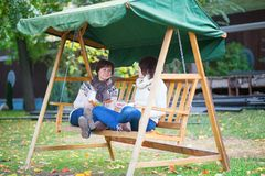 Middle aged woman with her daughter on a swing Royalty Free Stock Photos