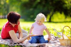 Middle aged woman and her little grandson having a picnic in park Royalty Free Stock Images