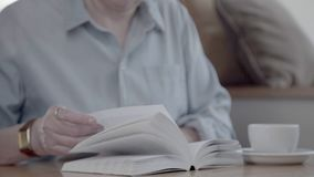 Middle-aged woman holding a book and turning the pages. stock video