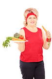 Middle aged woman holding carrot and plate full of vegetables Royalty Free Stock Image