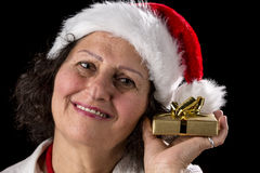 Middle-Aged Woman Holding Golden Gift. Smiling mature woman with a Santa Claus cap holding a Christmas present all wrapped in gold next to her left cheek. Pitch Stock Photo