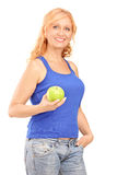 Middle aged woman holding a green apple and looking at camera Stock Photography