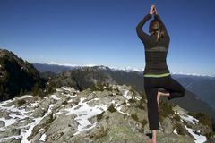 Middle-Aged Woman Holding Hatha Yoga Tree Pose on Winter Snowcap BC Mountain Peaks. Middle-Aged Caucasian Woman Holding Hatha Yoga Tree Pose on Winter Snowcap Royalty Free Stock Images