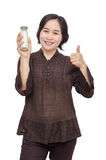 Middle aged woman holding milk bottle Stock Image