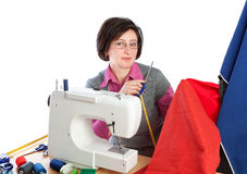 Middle-aged woman holding a pair of scissors at the sewing. Stock Photos