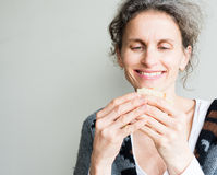 Middle aged woman holding sandwich. Middle aged woman with grey hair eating healthy looking salad sandwich (selective focus Stock Photos