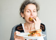 Middle aged woman holding sandwich plate. Middle aged woman with grey hair eating salad sandwich and holding plate (selective focus Stock Photo