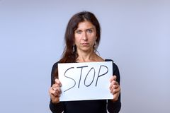 Mature woman holding white sheet with STOP lettering royalty free stock photos