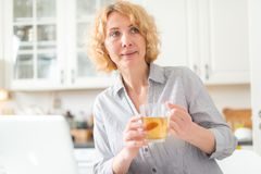 A middle-aged woman holds a cup of tea stock photography