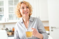 A middle-aged woman holds a cup of tea stock photo