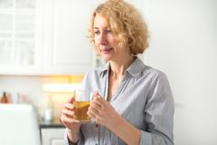 A middle-aged woman holds a cup of tea royalty free stock image