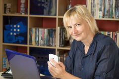 The middle aged woman at home office Stock Photography