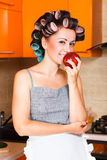 Middle-aged woman housewife in the kitchen with apple. Beautiful woman in the kitchen with apple Royalty Free Stock Photos