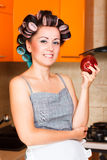 Middle-aged woman housewife in the kitchen with apple. Beautiful woman in the kitchen with apple Royalty Free Stock Images