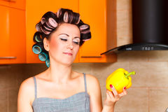Middle-aged woman housewife in kitchen looking with disgust at pepper. Beautiful woman in the kitchen looking with disgust at bell pepper Stock Photography