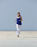 Middle aged woman jogging at the beach Royalty Free Stock Photo