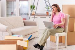 The middle-aged woman with laptop in home improvement concept. Middle-aged woman with laptop in home improvement concept royalty free stock photography