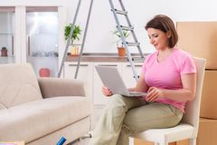 The middle-aged woman with laptop in home improvement concept. Middle-aged woman with laptop in home improvement concept royalty free stock image