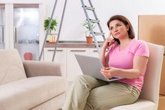 The middle-aged woman with laptop in home improvement concept. Middle-aged woman with laptop in home improvement concept stock photography