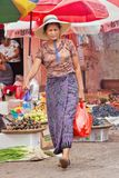 Middle-aged woman leaves a traditional market in Ruili, Yunnan Province, China. RUILI-CHINA-JUNE 28, 2014. Middle-aged woman leaves a market. Ruili is on the royalty free stock photography