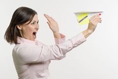 Middle-aged woman lets out a abstract paper airplane with the written word Addiction. Royalty Free Stock Photography