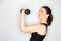 Middle aged woman lifting weights. Happy and proud middle aged woman in a black muscleshirt lifting dumbbell, light background, copy space Stock Image