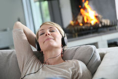 Middle-aged woman listening to music. Woman listening to music by fireplace Stock Image