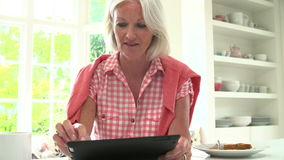 Middle Aged Woman Looking At Digital Tablet Over Breakfast stock footage
