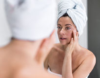Middle aged woman looking at herself in the mirror Stock Photography