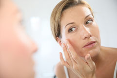 Middle-aged woman looking at the mirror and nourishing her skin Stock Photo