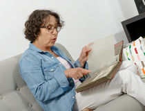 Middle-aged woman looking at photo album Royalty Free Stock Photo