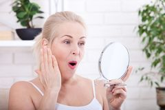 Middle aged woman looking at wrinkles in mirror. Plastic surgery and collagen injections. Makeup. Macro face. Selective focus Royalty Free Stock Image