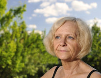 Middle-aged woman looks up at the sky. Stock Images