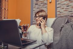 Middle aged woman making call and using laptop at home stock photo