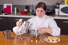 Middle-aged woman making tea in kitchen Royalty Free Stock Images