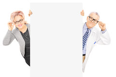 Middle aged woman and male doctor standing behind blank panel Royalty Free Stock Photos