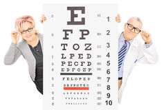 Middle aged woman and a male optician standing behind eyesight t Royalty Free Stock Image