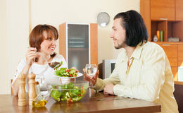 Middle-aged woman and man having vegetarian dinner at home. Positive middle-aged women and men having vegetarian dinner at home Royalty Free Stock Photos