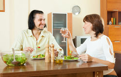 Middle-aged woman and a man on tasty vegetarianhaving dinner at. Positive middle-aged women and a men on tasty vegetarian Stock Image