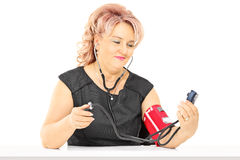 Middle aged woman measuring blood pressure. Isolated on white background Royalty Free Stock Photography