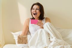 Middle aged woman in the morning in bed enjoys a gift. Reads card and happy. royalty free stock photo
