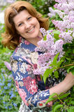 Middle-aged woman near blossoming lilac Royalty Free Stock Images