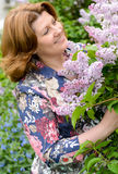 Middle-aged woman near blossoming lilac Stock Images