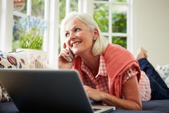 Middle Aged Woman Ordering Item On Telephone. Lying Down Relaxing And Using Laptop stock photo