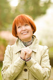 Middle-aged woman outdoors. Beautiful smiling middle-aged woman outdoors Stock Photos