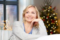 Middle aged woman over christmas tree at home stock photo