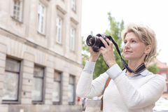 Middle-aged woman photographing through digital camera in city Royalty Free Stock Image