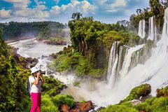 Middle-aged woman photographs. Middle-aged woman in red trousers and panama photographs grandiose waterfalls. Scenic basaltic rock formations famous waterfalls stock photo